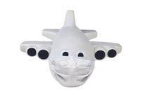 Covid-19 and travel restrictions concept. Toy Airplane with a surgical mask isolated on whte.
