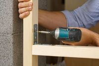 Craftman holds a portable screwdriver for fixing metal corners with screwing screws into the wood board.