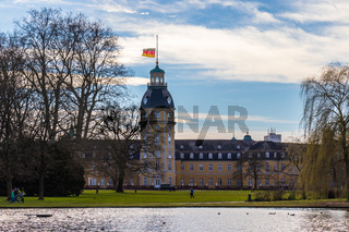 Castle Karlsruhe with Garden and Pond, and Flag and Halfmast, inside green Nature. District Karlsruhe, Baden-Württemberg, Germany