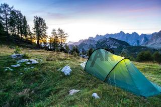 A tent glows under a moon night sky at twilight hour. Julian Alps, Triglav National Park, Slovenia.