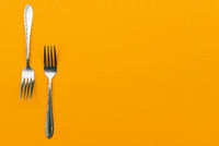 Two steel forks on an orange background. Cutlery for eating in a restaurant or at home. Stainless steel breakfast, lunch and dinner fork. Top view, copy space.