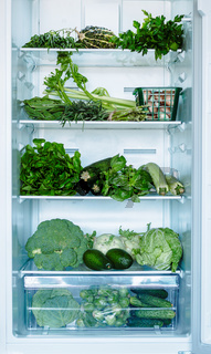 Green vegetables and greens in open refrigerator