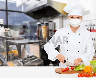 female chef in mask cutting vegetables at kitchen