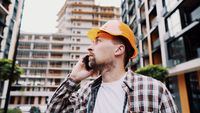 Engineer talking on phone. Architect using phone on construction site. Foreman phone call control process. Construction worker communications in construction industry. Building professional phone