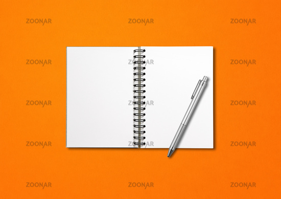 Blank open spiral notebook and pen isolated on orange