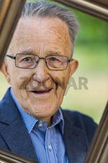 Pensioner looks through a picture frame