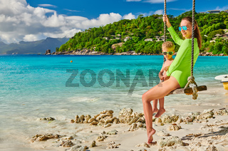 Woman swinging with son at tropical beach, Seychelles.