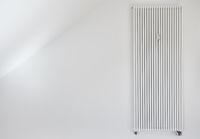 Heizung mit langem Röhrenheizkörper an Wand einer Wohnung