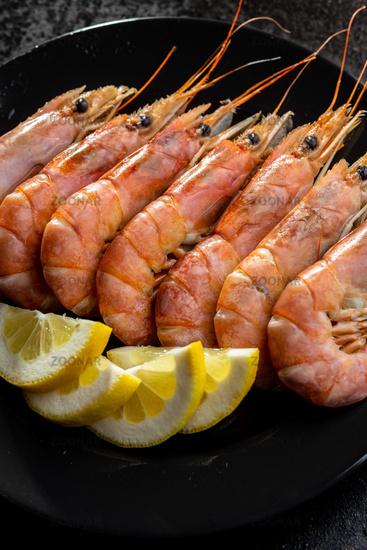 Boiled tiger prawns on black plate. Tasty shrimps.