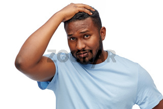 unhappy young african american man touching hair