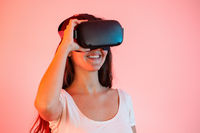 Young woman with virtual reality headset on eyes smiling from close up