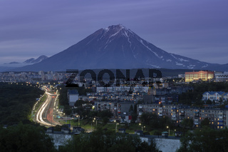 Summer night cityscape driving automobiles on city road on background of volcano