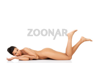 Attractive naked woman lying on the floor with legs up.