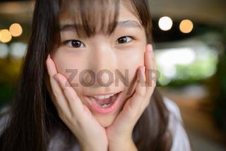 Young beautiful Asian teenage girl at the indoor garden