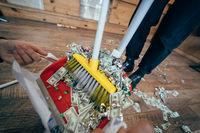 Broom sweeping dollars in scoop from on wooden floor