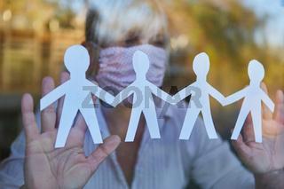 Seniorin hält Scherenschnitt ans Fenster während Covid-19 Pandemie