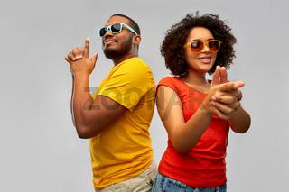 african couple in sunglasses makes finger gun