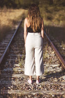 Old fashioned style photography. Back view, of of a woman standing on train tracks. concept of Choice or memories.