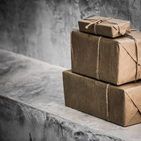 Parcels wrapped in brown paper in warehouse, packaged boxes for postal delivery service, concrete background with copyspace