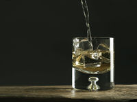 Glass of whiskey on a rustic wooden table