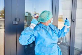 Reinigungskraft zuversichtlich beim Arbeiten vor einer Klinik während Coronavirus Pandemie