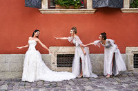 Beautiful bride and bridesmaids in gorgeous elegant stylish light grey silver floor length dresses in old beautiful European city having fun on a wedding day.