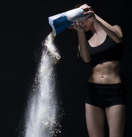 Slim girl pouring flour from packet on the floor