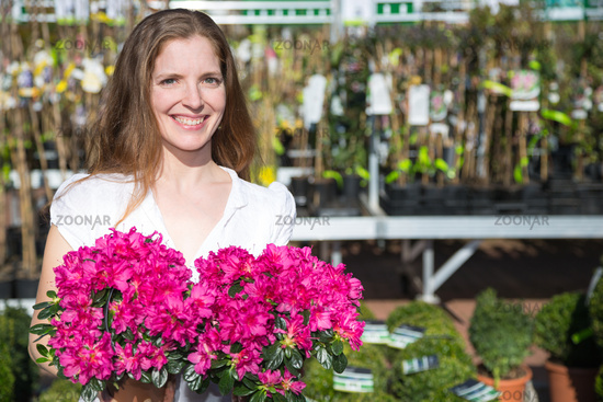 Customer at garden center or flower shop posing with bunch of flowers