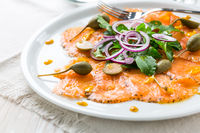 Salmon carpaccio and arugula salad with onions and capers on white plate