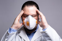 Frustrated medical doctor wearing a respiratory mask  touching his head with his hands. Burnout and