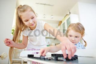 Zwei Kinder spielen mit Dominosteinen