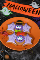 A couple (girl and boy) of funny, amusing  bat painted on honey gingerbread. Halloween food.