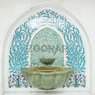 Tiled ornament drinking water fountains on forecourt of islamic mosque