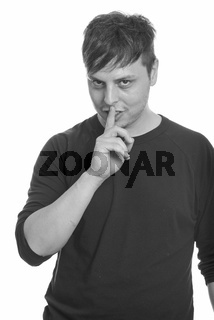 Studio shot of crazy Caucasian man with finger on lips