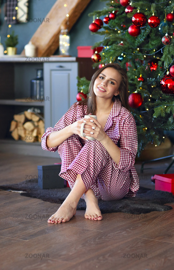 Charming young girl with drink in cozy kitchen