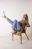 portrait of a beautiful young woman in jeans, shirt and sneakers.she put her feet up on the wicker rocking chair against the white brick wall.sitting on a chair