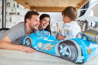 Lachende Eltern spielen mit Sohn im Kinderauto