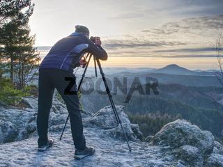 Hiker admiring stunning misty mountain range, sunny morning.