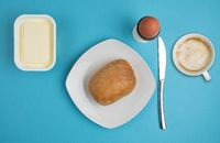 bread roll on plate, butter, boiled egg, knife and cup of coffee on blue background