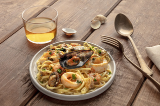 Seafood pasta. Tagliolini with mussels, shrimps, clams and squid rings, with a glass of wine on a rustic wooden background