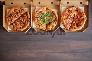 Three different kind of pizzas in delivery boxes