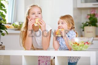 Kinder einer Familie essen Brötchen zum Frühstück