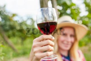 Blonde Frau hält ein Glas mit Rotwein