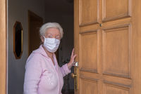 Senior woman with face mask in house quarantine