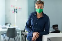 Caucasian man wearing face mask in an office