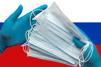 Doctor holds face masks in hands blue gloves on background national flag of Russia. Concept quarantine, hygiene, pandemic outbreak. Surgical antibacterial face bandage