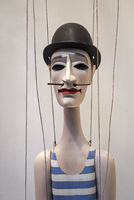 A wooden figure with a pointed beard and a bowler hat hangs on threads.