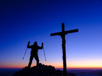 Silhouette of a mountain climber with a victory pose at the summit cross at dawn