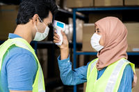 Islam Muslim asian warehouse worker take temperature to another worker