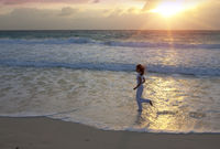 woman runs along the edge of the waves of a sandy beach at sunset